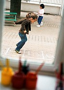 Children outdoors, one playing hopscotch, side view