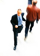 Businessman walking, elevated view, blurred