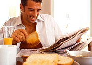 Man sitting reading newspaper, eating breakfast