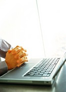 Businessman's folded hands on top of keyboard, close-up