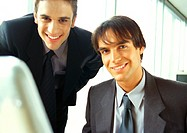 Businessmen smiling at camera, head and shoulders