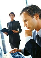 Businesswoman standing in backgroung, blurred, looking at businessman seated at computer