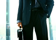 Businessman holding briefcase, hand in pocket, mid-section