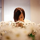 Daisies, blurred in foreground, woman smelling flowers in background