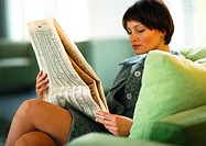 Businesswoman sitting with legs crossed, reading paper (thumbnail)