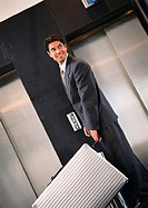 Businessman standing near elevators with suitcase, looking over shoulder