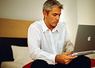 Businessman sitting on bed using laptop