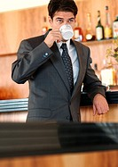 Businessman standing at bar, drinking out of coffee cup