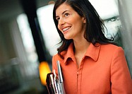 Businesswoman holding agenda and file, smiling