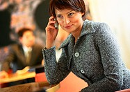 Businesswoman sitting, listening to cell phone, tilt