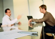 Businessmen working together in office space, blurred