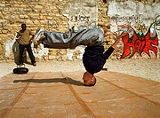 Man balancing on head, break dancing, man in background watching