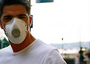 Man wearing white dust mask over nose and mouth, blurred background