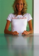 Woman wearing 'keep in touch' t-shirt, winking and smiling