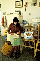Elderly woman breaking almonds at interior of rural house. Lassithi plateau, Crete. Greece