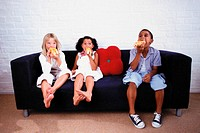 Boy and girl eating on sofa