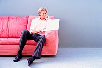 Man on sofa using laptop computer