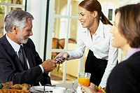 Waitress handing cellphone to businessman
