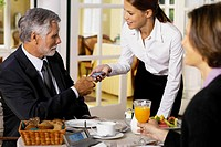 Businessman and businesswoman having breakfast