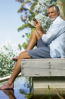 Man beside pool with cellphone