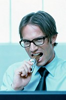 Businessman eating a chocolate bar