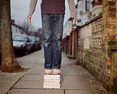 A young man standing on a pile of books
