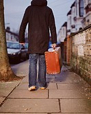 A young man carrying a leather suitcase