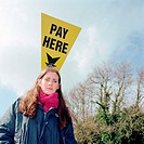 Girl standing by Pay Here sign