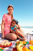 Mum and daughter having a picnic on a beach