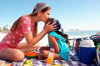 Mum kissing daughter on a beach