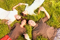 People lying in circle on grass