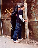 Teenage boys peering through wall (thumbnail)