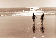Silhouette of Two Children Running on the Beach