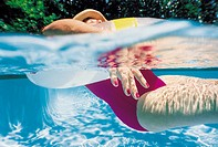 Half-Submerged Woman Lying in a Swimming Pool with an Inflatable