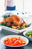 Roast Turkey and Vegetables with a Woman Preparing Christmas Dinner in the Background