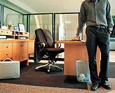 Man Standing Next to His Desk in the Office