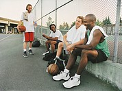 Four Male Basketball Players Relaxing on a Basketball Court and Having a Discussion