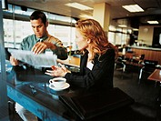 Businesswoman Talking to a Businessman Reading a Newspaper at a Bar Counter