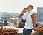 Businessman Wearing Sportswear Standing Outdoors on a Balcony Talking on His Mobile Phone