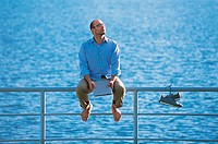 Barefoot Businessman Sitting Next to a Pair of Trainers Hanging From a Railing By the Sea