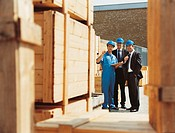Businessmen and a Factory Worker Talking and Looking at Crates