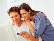 Couple Using their Bank Card for Home Shopping on the World Wide Web