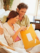 Couple Sitting on a Sofa in their Sitting Room and Opening a Parcel