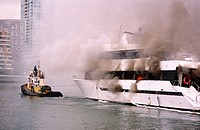 Tug boat tows a burning luxury yacht away from the dock. Granville Island, Vancouver. Canada