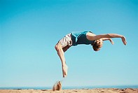 Young man doing a back flip on the beach (thumbnail)