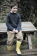 Portrait of a young boy sitting on a garden table (thumbnail)
