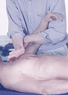 Male physiotherapist massaging and stretching patient with naked torso (thumbnail)