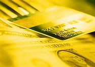Yellow duotone closeup of American banknotes with credit card (thumbnail)