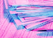 Banknotes laid in neat pile on top of financial pages of newspaper with pen (thumbnail)