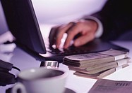 Closeup of buinessman's hand typing on keyboard of laptop computer with wads of banknotes (thumbnail)